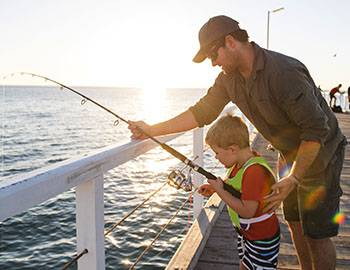 father and son fishing together on the pier