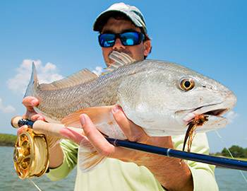 Man holding a redfish at the fishing pier