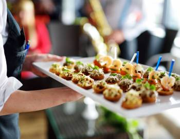 A server holds a plate of appetizers