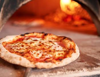 A pizza is brought out of the oven