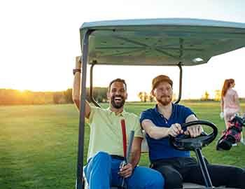 Two guys riding on a golf cart together smiling