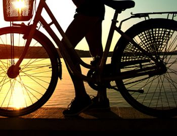 Girl with cruiser bike at sunset