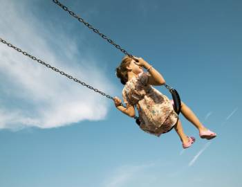 A girl sits on a swing set