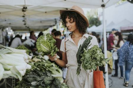 A woman grabs some produce at a local farmers market