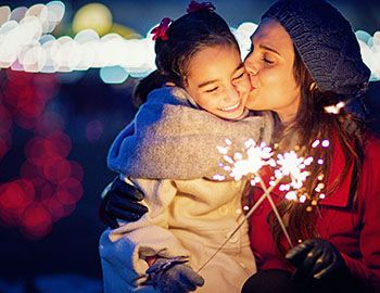 Mom and daughter holding sparklers at a holiday lights display