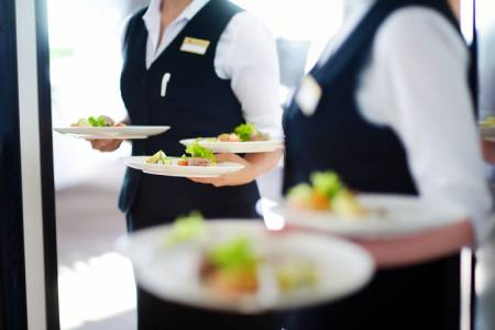 Staff carry plates while catering a wedding
