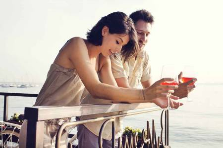 Husband and wife enjoying a spritzer on a yacht
