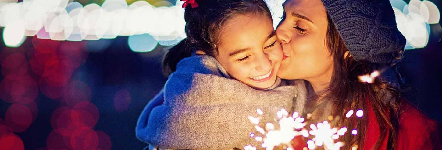 Mom and daughter dazzled at a holiday lights display