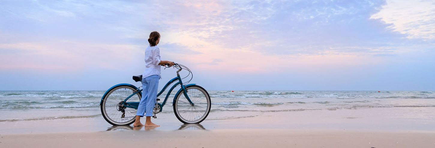 Woman with her bike on a beach at sunset