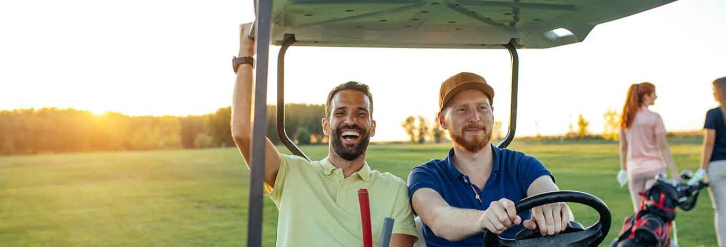 Two guys riding a golf cart together and smiling on Hilton Head