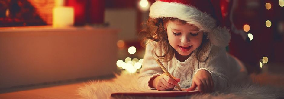Little girl writing a Christmas letter to Santa by the Christmas tree