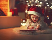 Little girl writing a Christmas letter to Santa by the tree