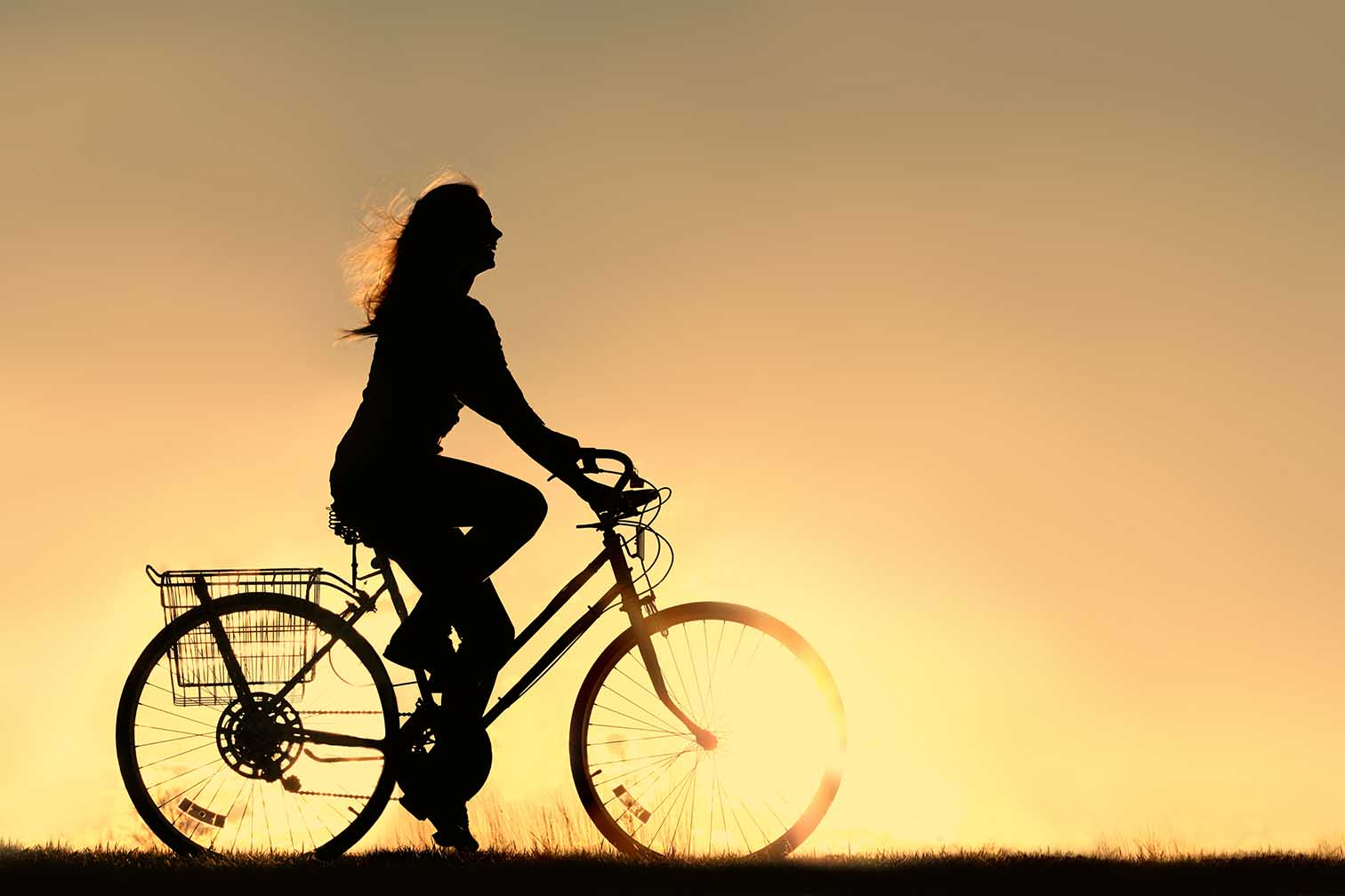 woman riding bike at sunset