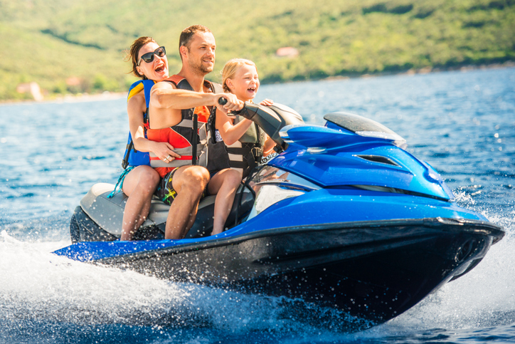 young family with kid on jet skis in tropical destination