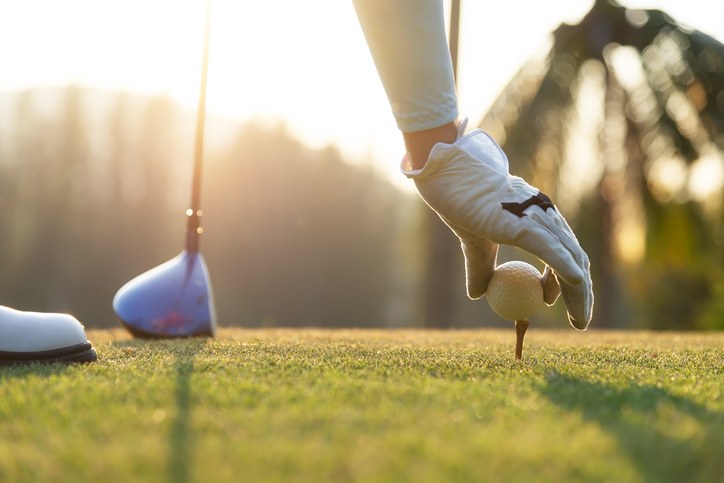 A golfer puts a ball on the tee
