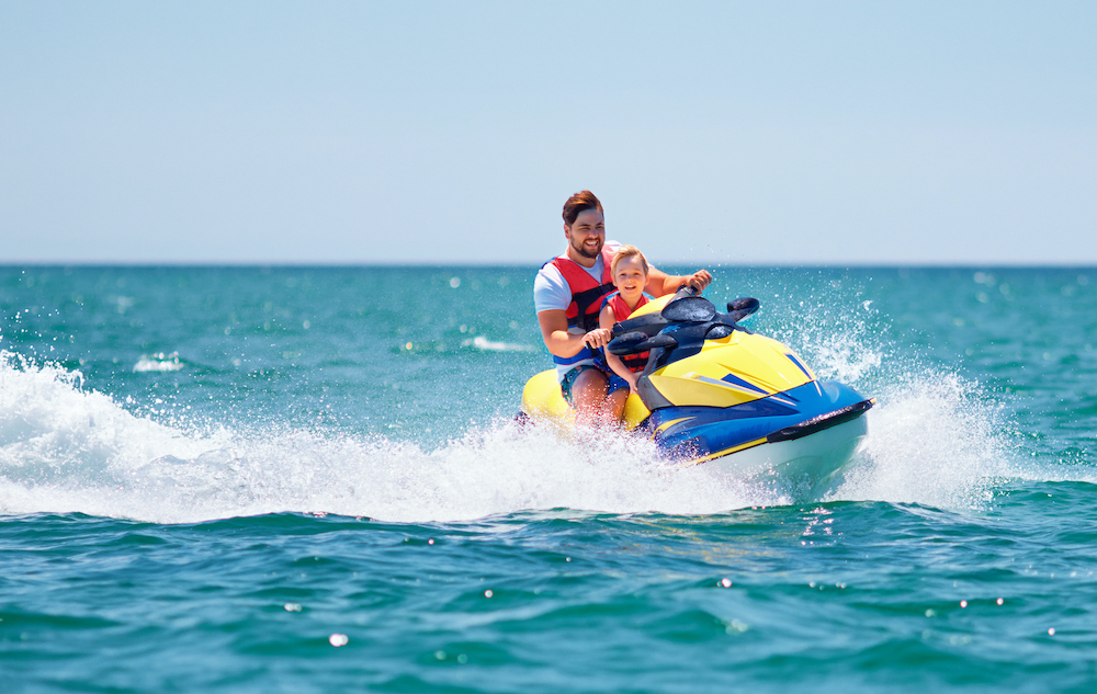A father and son enjoy a ride on a jet ski