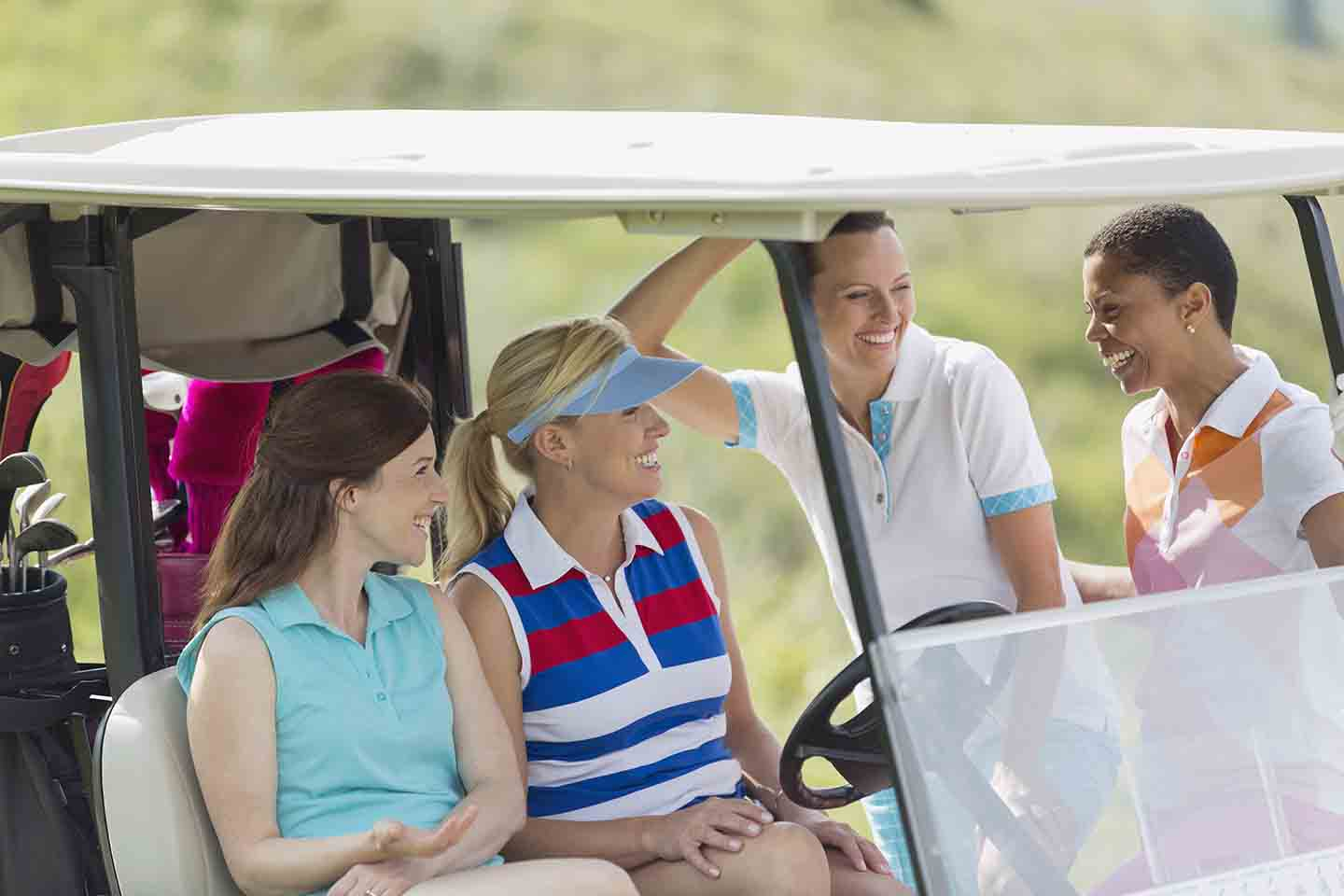 Friends standing around a golf cart conversing
