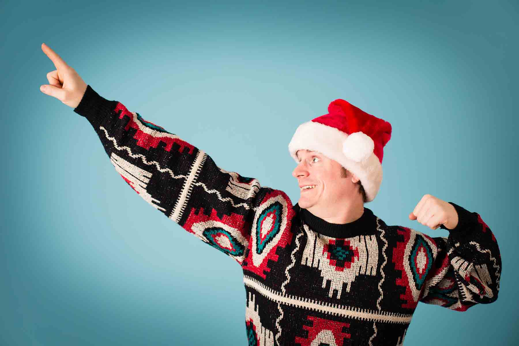 Man wearing ugly Christmas sweater and Santa hat